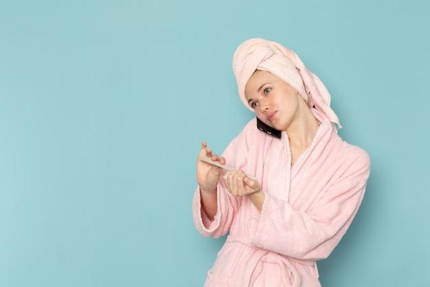 Jonge vrouw in roze badjas na douche praten over de telefoon tot vaststelling van haar nagels op blauw