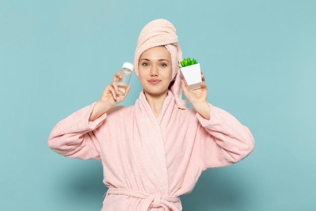 Jonge vrouw in roze badjas na het douchen met groene plantenspray op blauw