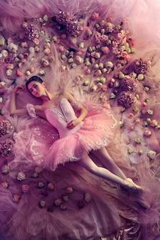 Jonge vrouw in roze ballet tutu omgeven door bloemen