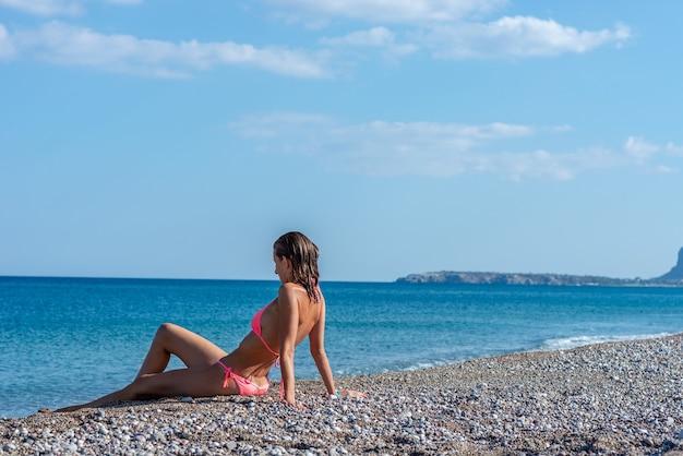 Jonge vrouw in roze bikini en natte haren zittend op een prachtig kiezelstrand door blauwe griekse zee.