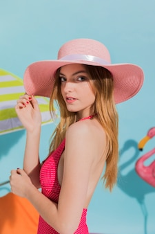 Jonge vrouw in roze hoed en zwembroek poseren