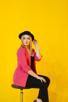 Jonge vrouw in roze jas zittend op stoel op geel