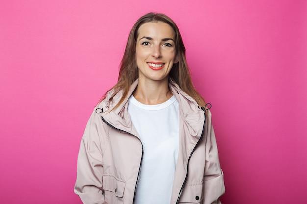 Jonge vrouw in roze jasje, roze geïsoleerde achtergrond.