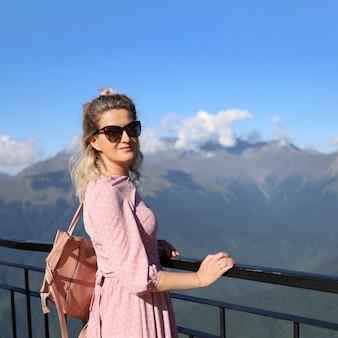 Jonge vrouw in roze jurk en zonnebril vormt tegen de achtergrond van bergen