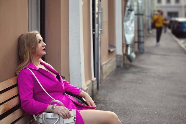 Jonge vrouw in roze kleren zit op bankje in het midden van de stad straat.
