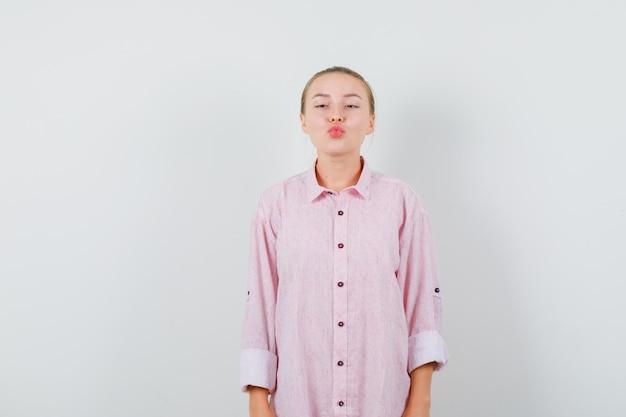 Jonge vrouw in roze overhemd die lippen gevouwen houden en geconcentreerd kijken