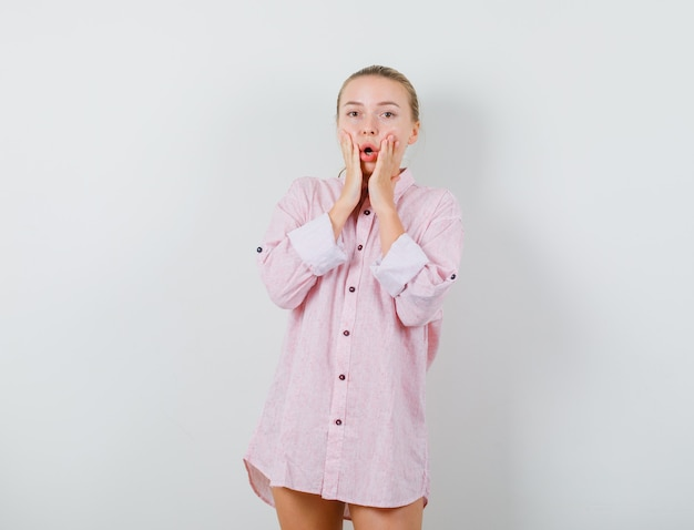 Jonge vrouw in roze overhemd hand in hand op wangen en op zoek verrast
