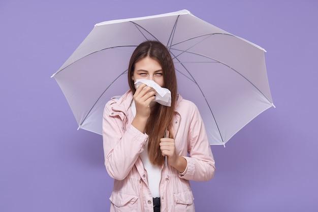 Jonge vrouw in roze regenjas die mond bedekt met zakdoek, die zich voordeed onder witte paraplu die over lila muurachtergrond wordt geïsoleerd, met loopneus, ziek zijn, nat weer.