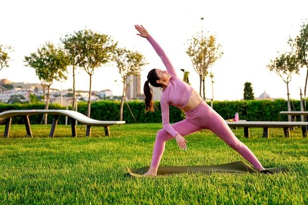 Jonge vrouw in roze shirt en broek op het gras in groen park mediteren en yoga doen in verschillende poses