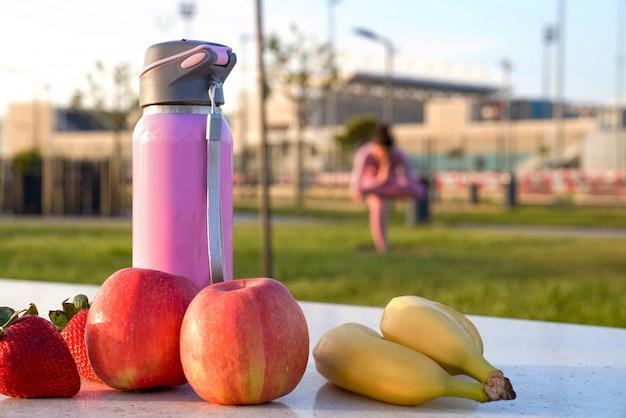 Jonge vrouw in roze shirt en broek op het gras in park fruit fles mediteren en yoga doen in verschillende poses