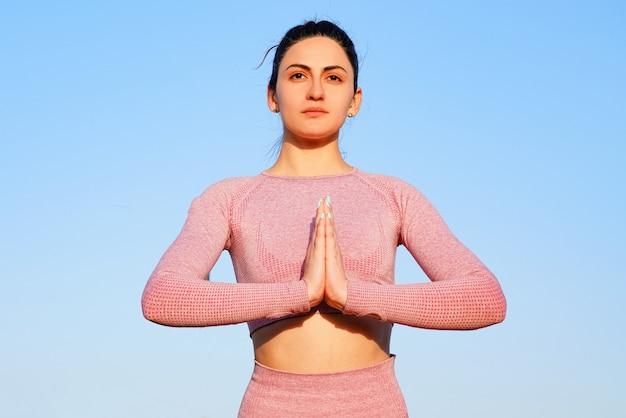 Jonge vrouw in roze shirt en broek op het gras overdag in groen park mediteren en yoga doen in verschillende poses