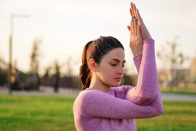 Jonge vrouw in roze shirt en broek zittend op het gras in het park mediteren en yoga doen in verschillende poses