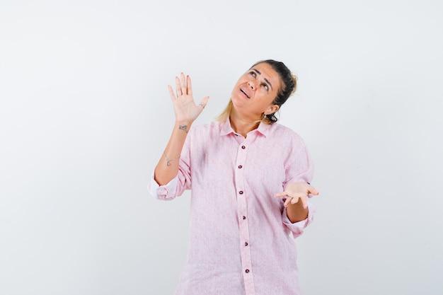 Jonge vrouw in roze shirt met open handen opzoeken en hoopvol kijken
