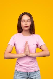 Jonge vrouw in roze t-shirt en spijkerbroek handen omklemd en ogen sluiten tijdens meditatieproces