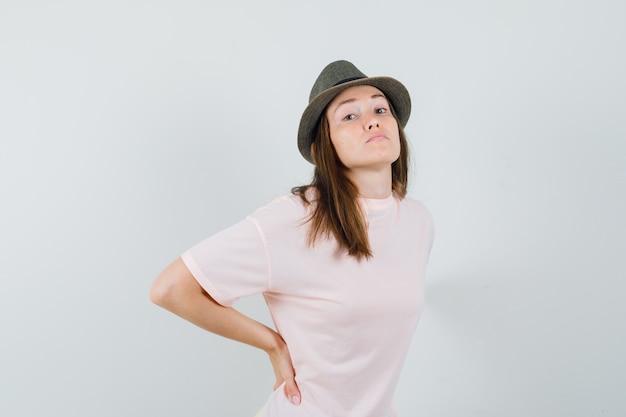 Jonge vrouw in roze t-shirt, hoed die aan rugpijn lijdt en moe, vooraanzicht kijkt.
