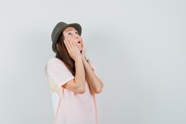 Jonge vrouw in roze t-shirt, hoed hand in hand op wangen en op zoek verbaasd, vooraanzicht.