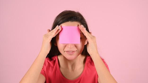 Jonge vrouw in roze t-shirt met een stuk papier op haar voorhoofd, ruimte voor inscriptie. . hoge kwaliteit foto
