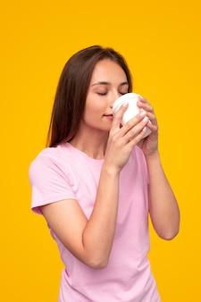 Jonge vrouw in roze t-shirt ogen sluiten en genieten van de geur van vers gezette koffie om in de ochtend te gaan