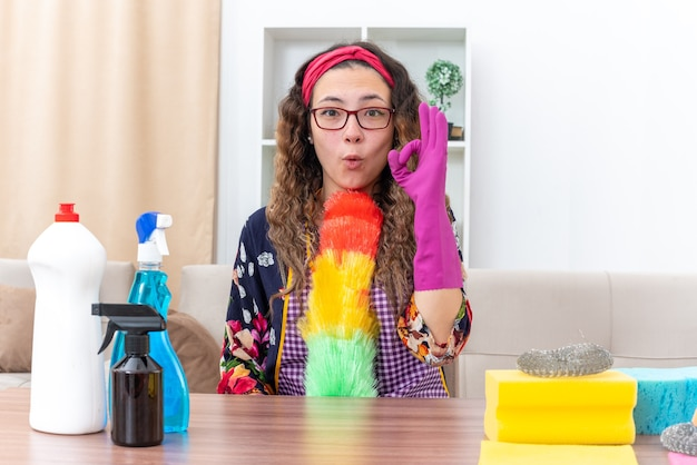 Jonge vrouw in rubberen handschoenen met statische stofdoek blij en verrast doen ok teken zittend aan de tafel met schoonmaakbenodigdheden en gereedschap in lichte woonkamer