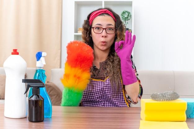 Jonge vrouw in rubberen handschoenen met statische stofdoek doet ok teken gelukkig en positief zittend aan de tafel met schoonmaakbenodigdheden en gereedschap in lichte woonkamer