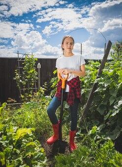 Jonge vrouw in rubberen laarzen aan het werk in de achtertuin