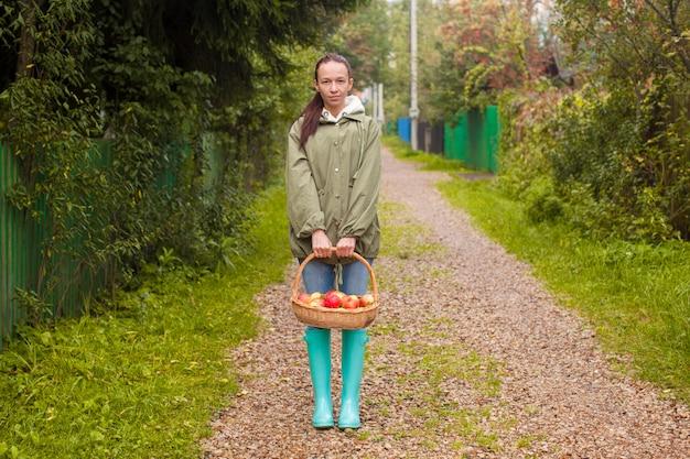 Jonge vrouw in rubberlaarzen met mand van appelen in de handen in de herfsttijd