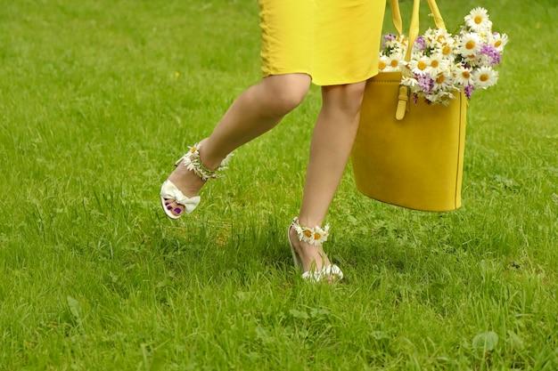 Jonge vrouw in sandalen met madeliefjes aan haar voeten en bloemen in een gele zak lopen.