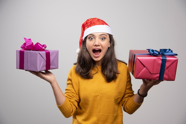 Jonge vrouw in santa hoed bedrijf in handen kerstcadeautjes.