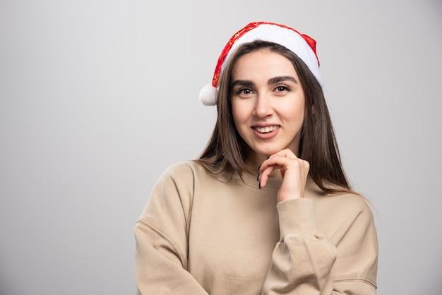 Jonge vrouw in santa's hoed poseren studio-opname geïsoleerd op grijs.