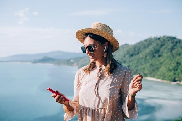 Jonge vrouw in schattige zomerjurk, strooien hoed en zonnebril dansen met smartphone bij de hand en luisteren naar muziek