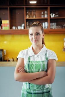Jonge vrouw in schort die in koffiewinkel werkt