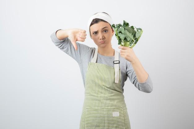 Jonge vrouw in schort die verse broccoli houdt en duimen naar beneden geeft