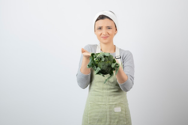 Jonge vrouw in schort die verse broccoli op wit houdt