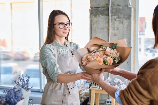 Jonge vrouw in schort en brillen groot boeket van pastel bloemen geven aan haar klant in de bloemist winkel