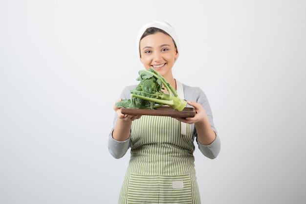 Jonge vrouw in schort met bord broccoli op wit
