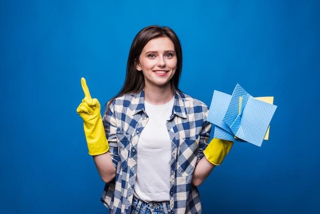 Jonge vrouw in schort met omhoog geïsoleerde vinger. goed idee om schoon te maken. schoonmaak concept