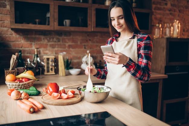 Jonge vrouw in schort mobiele telefoon gebruiken tijdens het koken van groentesalade in de keuken. bereiding van verse dieetvoeding. vrouw bereidt een romantisch diner voor haar man