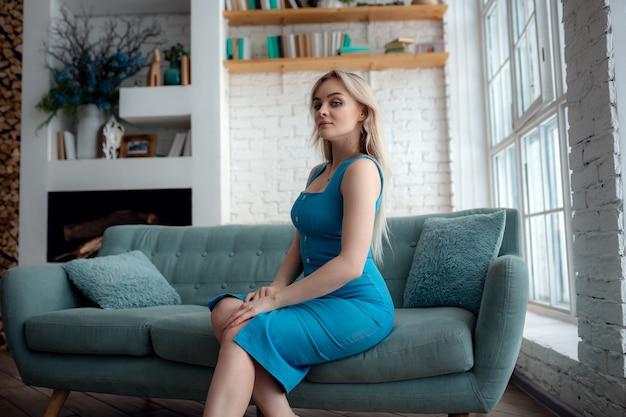 Jonge vrouw in sexy jurk zit op een bank. sensuele mooie blonde vrouw poseren in blauwe jurk. meisje met lang haar. binnen schot.