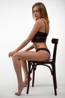 Jonge vrouw in sexy kanten ondergoed zittend op een stoel
