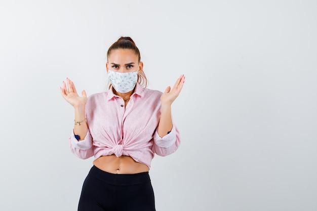 Jonge vrouw in shirt, broek, medisch masker spreidt handpalmen in clueless gebaar en kijkt hulpeloos, vooraanzicht.