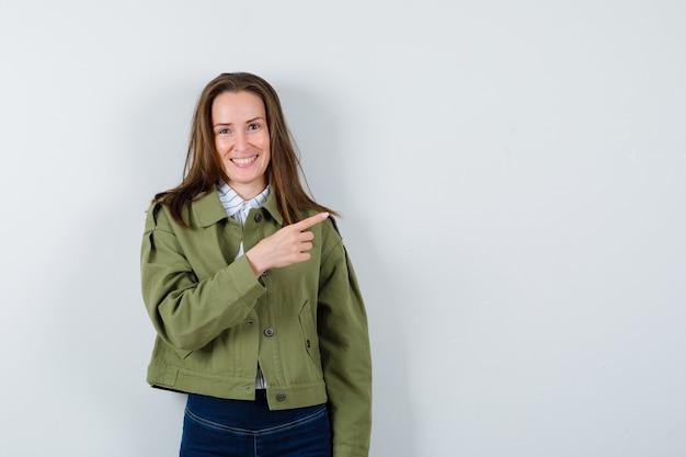 Jonge vrouw in shirt, jas opzij wijzend en vrolijk, vooraanzicht.