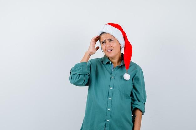 Jonge vrouw in shirt, kerstmuts die lijdt aan hoofdpijn en er pijnlijk uitziet, vooraanzicht.