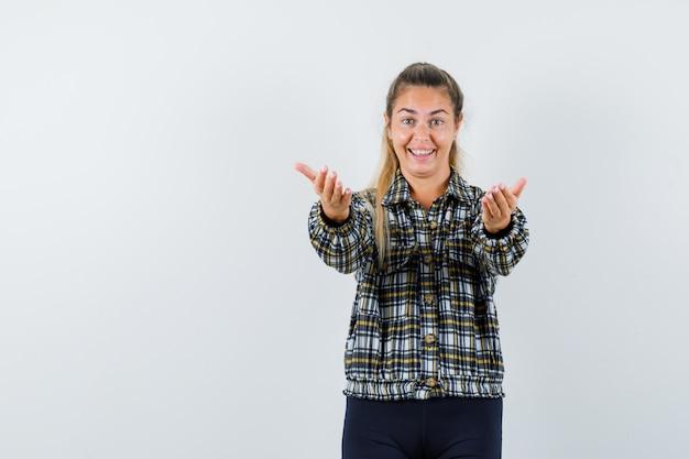 Jonge vrouw in shirt, korte broek die uitnodigt om te komen en er vrolijk uitziet, vooraanzicht.