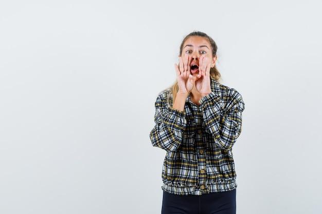 Jonge vrouw in shirt, korte broek schreeuwen of iets aankondigen, vooraanzicht.