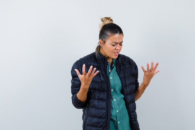 Jonge vrouw in shirt, pufferjack die handen opsteekt, naar beneden kijkt en weemoedig kijkt, vooraanzicht.