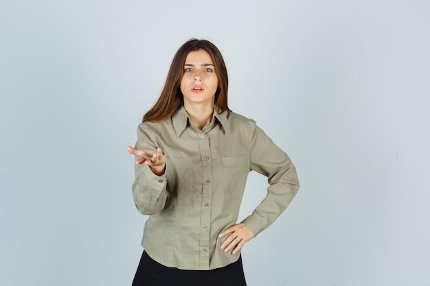 Jonge vrouw in shirt, rok die een vraaggebaar maakt en verbaasd kijkt, vooraanzicht.