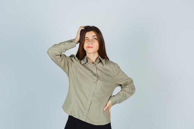 Jonge vrouw in shirt, rok die hoofd krabt terwijl ze de lippen buigt, omhoog kijkt en peinzend kijkt, vooraanzicht.