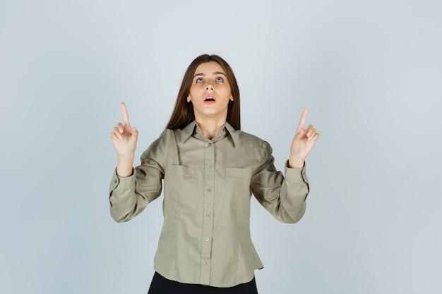 Jonge vrouw in shirt, rok die omhoog wijst en er hoopvol uitziet, vooraanzicht.