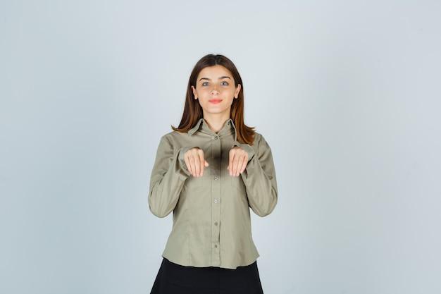 Jonge vrouw in shirt, rok hand in hand als poten over de borst en ziet er prachtig uit