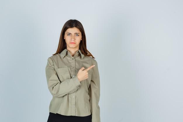 Jonge vrouw in shirt, rok wijzend naar de rechterbovenhoek, gebogen onderlip en beledigd kijkend, vooraanzicht.